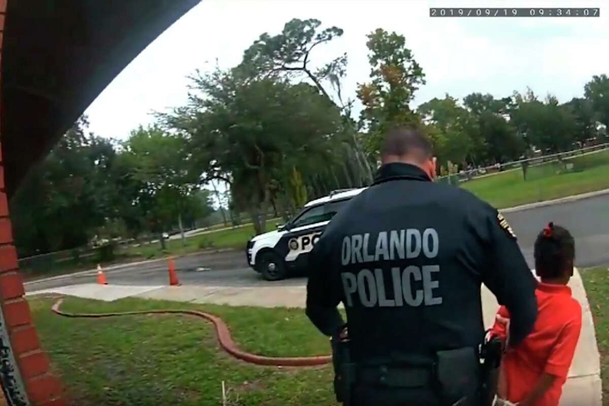 In this image taken from Sept. 19, 2019, Orlando Police Department body camera video footage, Orlando Police Officer Dennis Turner leads 6-year-old Kaia Rolle away after her arrest for kicking and punching staff members at the Lucious & Emma Nixon Academy Charter School in Orlando, Fla. Turner was fired shortly after the arrest for not getting the approval of a watch commander to arrest someone younger than 12. (Orlando Police Department/Orlando Sentinel via AP)