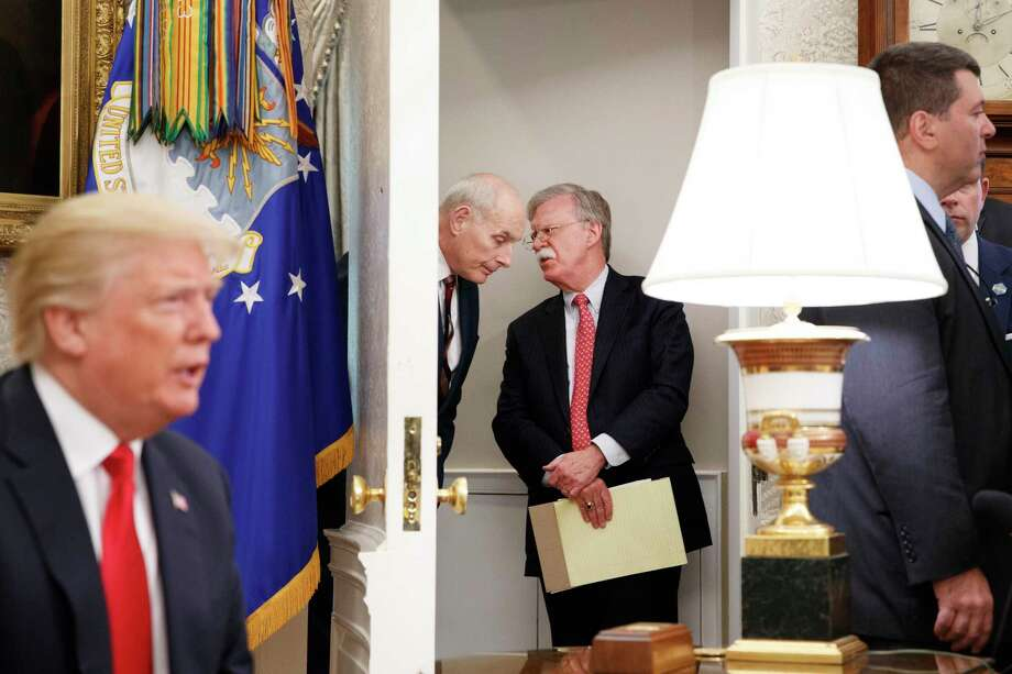 FILE -- Former Chief of Staff Gen. John Kelly whispers to former National Security Adviser John Bolton outside the Oval Office at the White House in Washington, April 30, 2018. After more than three years of the Trump presidency, it has become easy to forget at times just how out of the ordinary it really is. (Tom Brenner/The New York Times) Photo: TOM BRENNER, STF / NYT / NYTNS