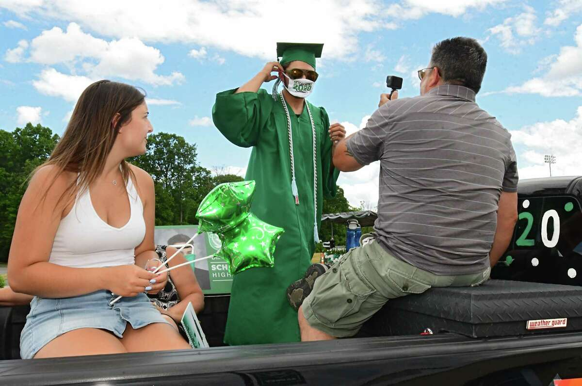 Graduate Dillon DiGirolamo puts on his face mask in the back of his family's pickup truck as graduates pick up their diplomas during a drive through graduation at Schalmont High School on Friday, June 19, 2020 in Rotterdam, N.Y. (Lori Van Buren/Times Union)