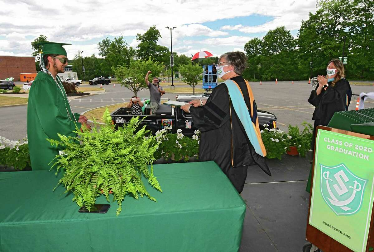 Graduate Dillon DiGirolamo receives his diploma from Superintendent Dr. Carol Pallas as graduates pick up their diplomas during a drive through graduation at Schalmont High School on Friday, June 19, 2020 in Rotterdam, N.Y. Dillon's family records the special moment from their truck.(Lori Van Buren/Times Union)