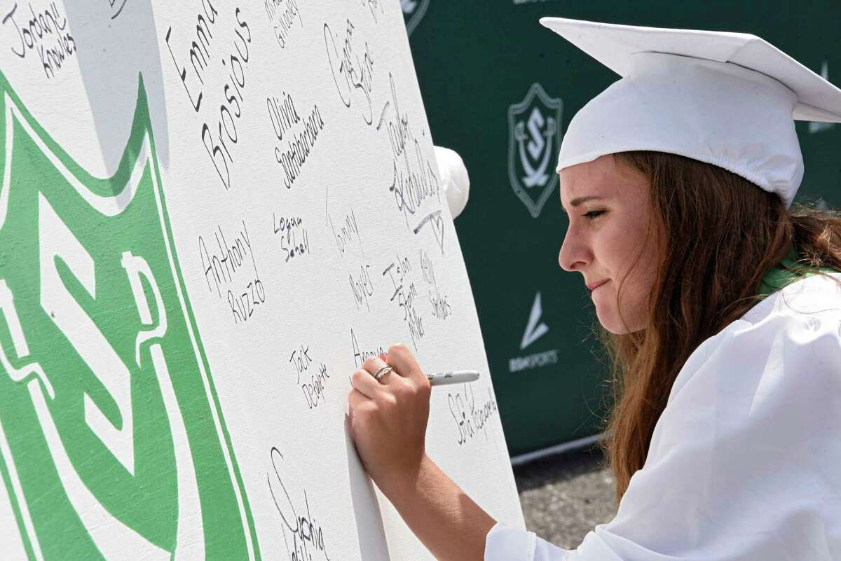 Graduate Amaya DiGiovanni signs a class poster while graduates pick up their diplomas as Schalmont Central School District holds a drive through graduation at Schalmont High School on Friday, June 19, 2020 in Rotterdam, N.Y. (Lori Van Buren/Times Union)