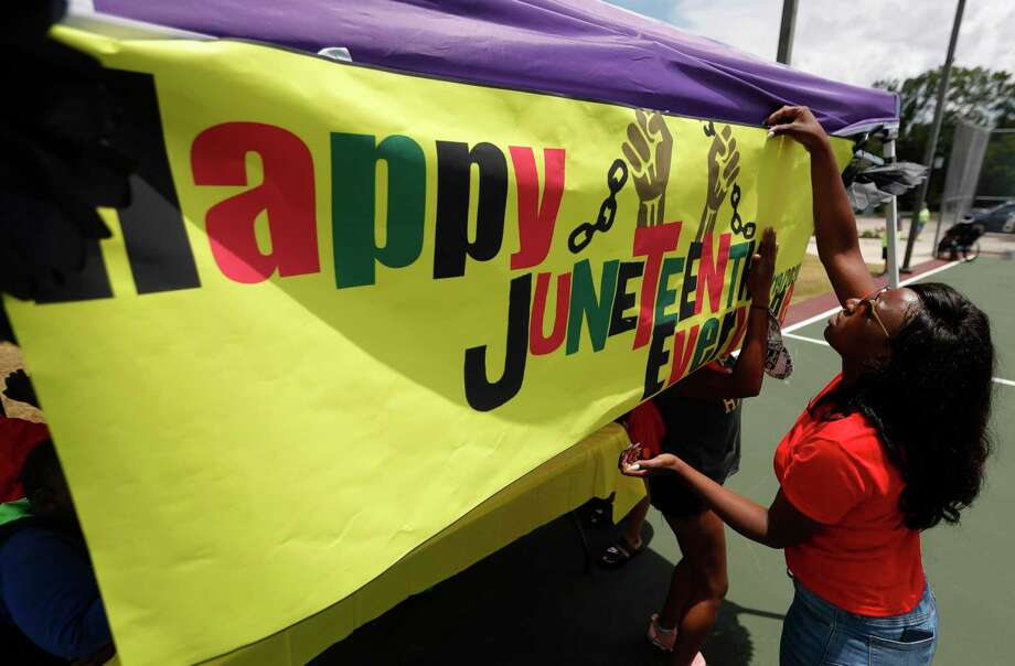 Areisha Harris puts up a Junteenth sign during Good Brothers & Sisters of Montgomery County's inaugural Juneteenth celebration at Martin Luther King, Jr. Park on Friday, in Conroe. Photo: Jason Fochtman, Houston Chronicle / Staff Photographer / 2020 © Houston Chronicle