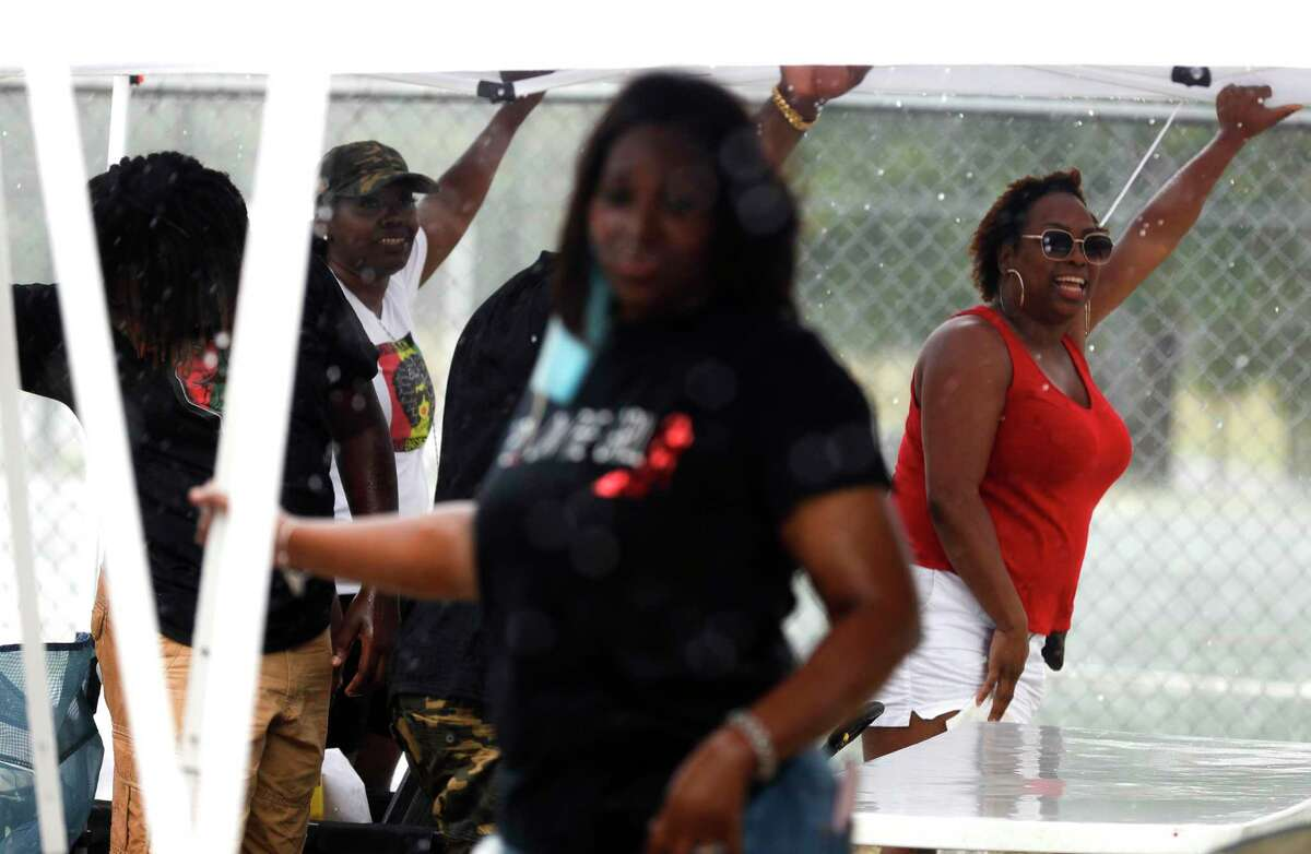 Antunette Whitaker, right, shares a laugh as she helps other business owners hold down their tents in the pouring rain during Good Brothers & Sisters of Montgomery County's inaugural Juneteenth celebration at Martin Luther King, Jr. Park, Friday, June 19, 2020, in Conroe. Juneteenth celebrates when Union General Gordon Granger read the federal orders that freed previously enslaved people in Texas in 1865, two years after President Abraham Lincoln signed the Emancipation Proclamation.
