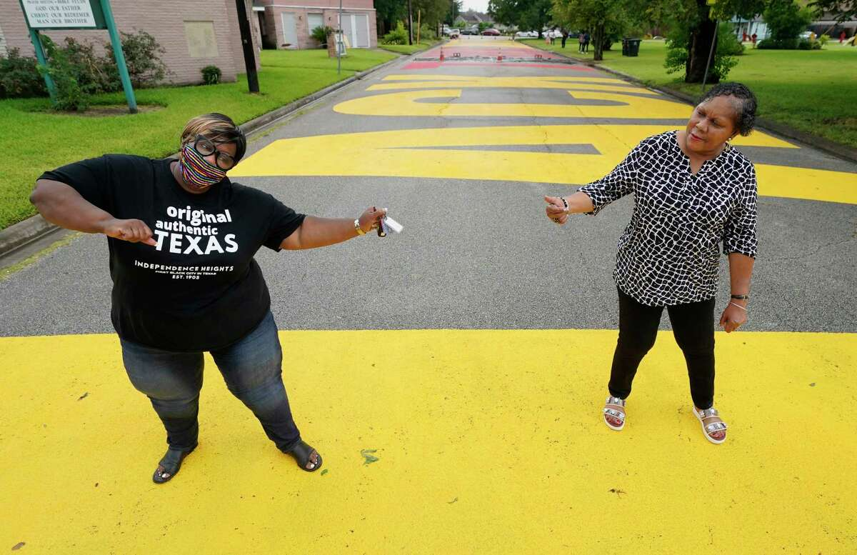"""Tanya Debose, Independent Heights civic leader, left, and Shirley Jones, right, dance on Link Road that is painted with the slogan """"Black Towns Matter"""" in celebration of Juneteenth in Independent Heights Friday, June 19, 2020, in Houston. They were dancing to """"Cupid Shuffle"""" being played by a DJ at the nearby free food distribution outside of Ebenezer United Methodist Church that was part of the """"Black Towns Matter"""" event."""