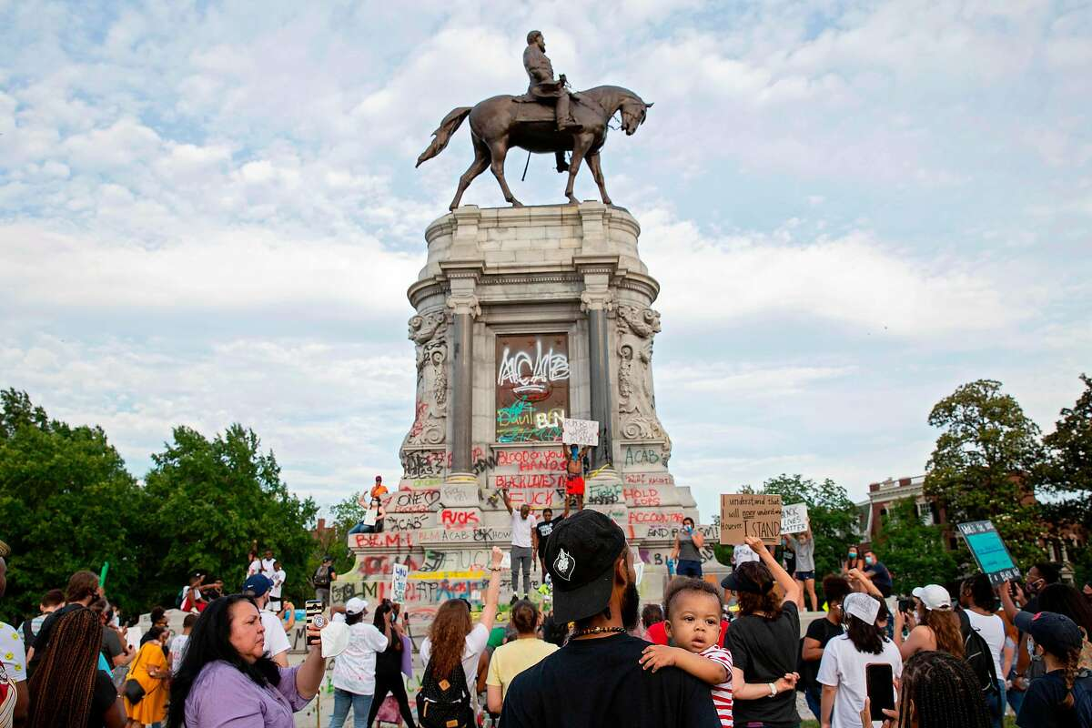 """People gather around the Robert E. Lee statue on Monument Avenue in Richmond, Virginia, on June 4, 2020, amid continued protests over the death of George Floyd in police custody. - Earlier in the day, Virginia governor Ralph Northam announced plans to remove the statue of the Confederate general, directing the Department of General Services to remove it """"as soon as possible."""" (Photo by Ryan M. Kelly / AFP) (Photo by RYAN M. KELLY/AFP via Getty Images)"""