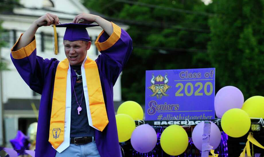 Alex Edwards attaches his tassel as he has a photo taken while parents, families and friends cheer on Seniors of Westhill High School as 500+ graduates parade into the school parking lot to celebrate the Class of 2020 Graduation on June 19, 2020 in Stamford, Connecticut. Photo: Matthew Brown / Hearst Connecticut Media / Stamford Advocate
