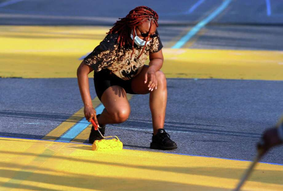 "As part of the celebration of Juneteenth, Latoya Radway, of Bridgeport, takes part in painting the words ""Black Lives Matter"" onto Broad Street in downtown Bridgeport, Conn., on Friday June 19, 2020. The event was organized by Sheree Baldwin-Muhammad and involved local artists, community members, local officials and residents to paint the words. Photo: Christian Abraham / Hearst Connecticut Media / Connecticut Post"