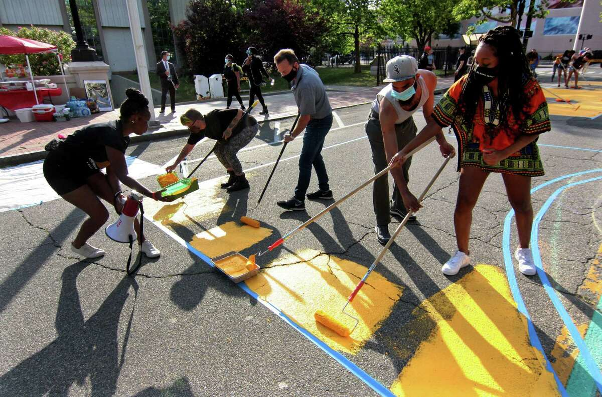 Mayor Joe Ganim, top center, takes part of the celebration of Juneteenth, by helping to paint the words