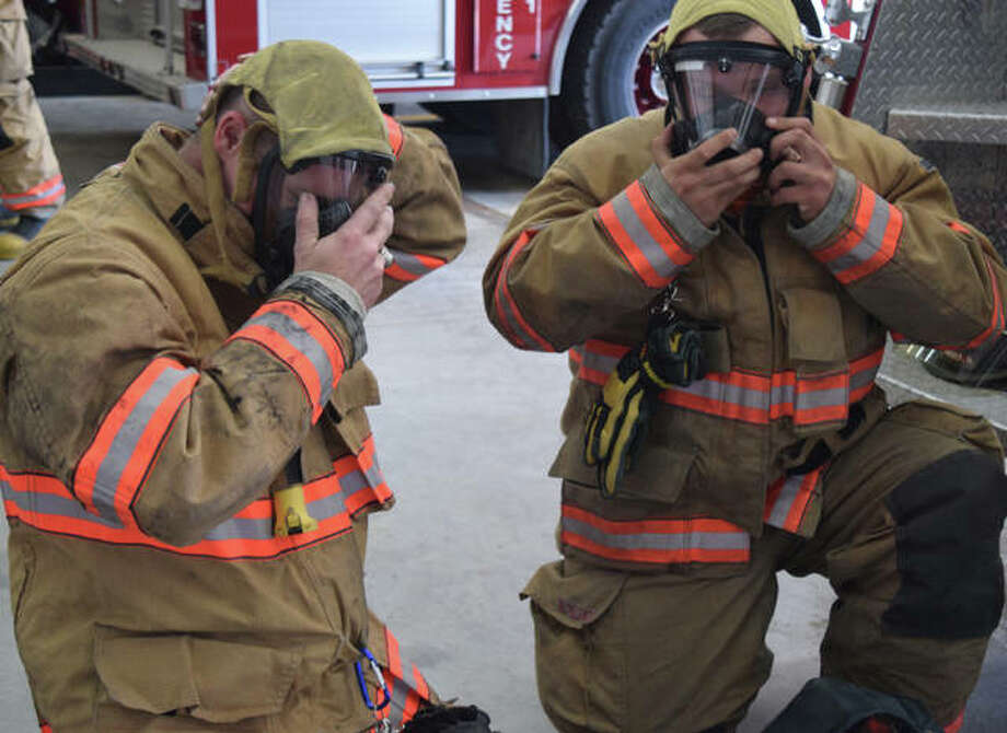 Waverly Volunteer Fire Department Assistant Chief Michael Brown (left) shows firefighter Brett Rumple how to secure his air mask June 13 during the department's first in-person training session since the state's stay-at-home order took effect.