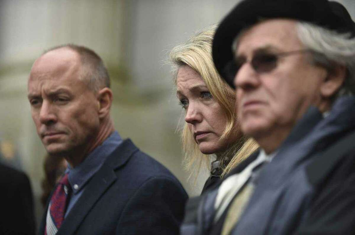 From left, Mark Barden, Nicole Hockley and Gilles Rousseau listen during a press conference on the steps of the state Supreme Court after attending a hearing in a lawsuit against Remington Arms in Hartford, Conn., Tuesday, Nov. 14, 2017.
