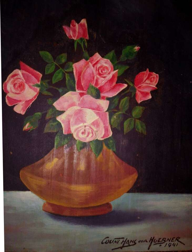 """This still life of pink roses in a golden-brown vase, painted in oil on wood, is signed """"Count Hans von Huebner."""" Hans Huebner, born in Europe in the late 1800s, was an employee in glass manufacturing plants who lived in New York, Ohio, back in New York and then San Antonio. Later in life, he claimed to have studied art with """"masters"""" in Munich and added """"count"""" and """"von"""" to his name, achieving a measure of success as an artist."""