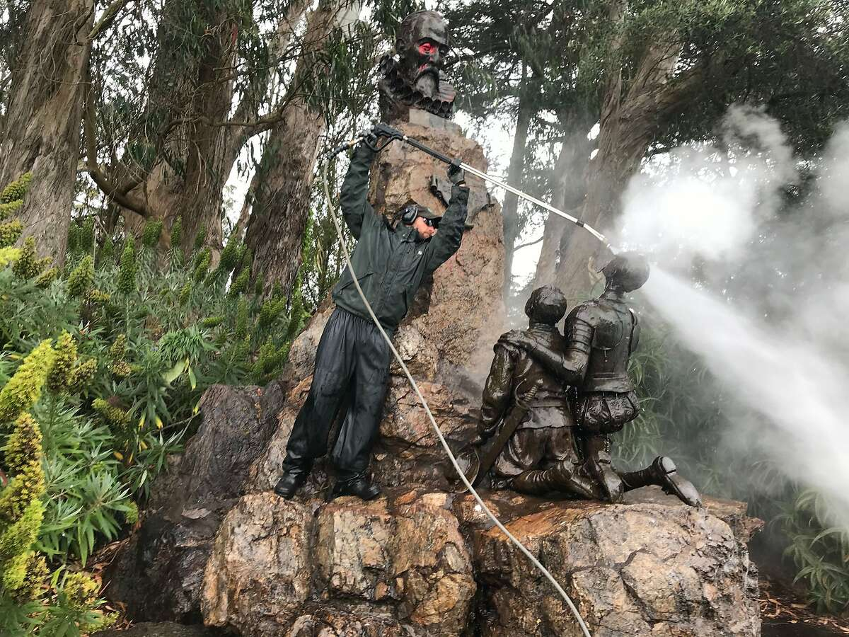 Groundskeeper James McCormick of San Francisco Recreation and Parks steam cleans red paint off Don Quixote