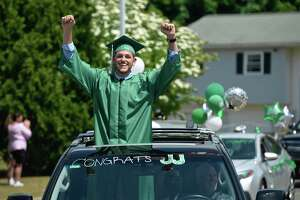 Graduate Justin Michael Jennings arrives at the 2020 New Milford High School graduation ceremony on Saturday. The graduates paraded from Sarah Noble Intermediate School to the high school and walked the sidewalk to receive their diplomas. June 20, 2020, in New Milford, Conn.
