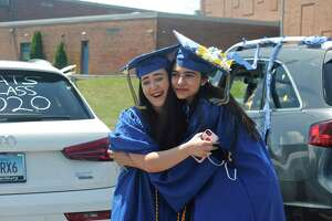 Maria Maciel and Marrium Mufti hug outside of the high school after not seeing each other for months. Brookfield High School graduates paraded from Whisconier Middle School to the high school where they received their diplomas, a goodie bag and posed for pictures on June 20, 2020.