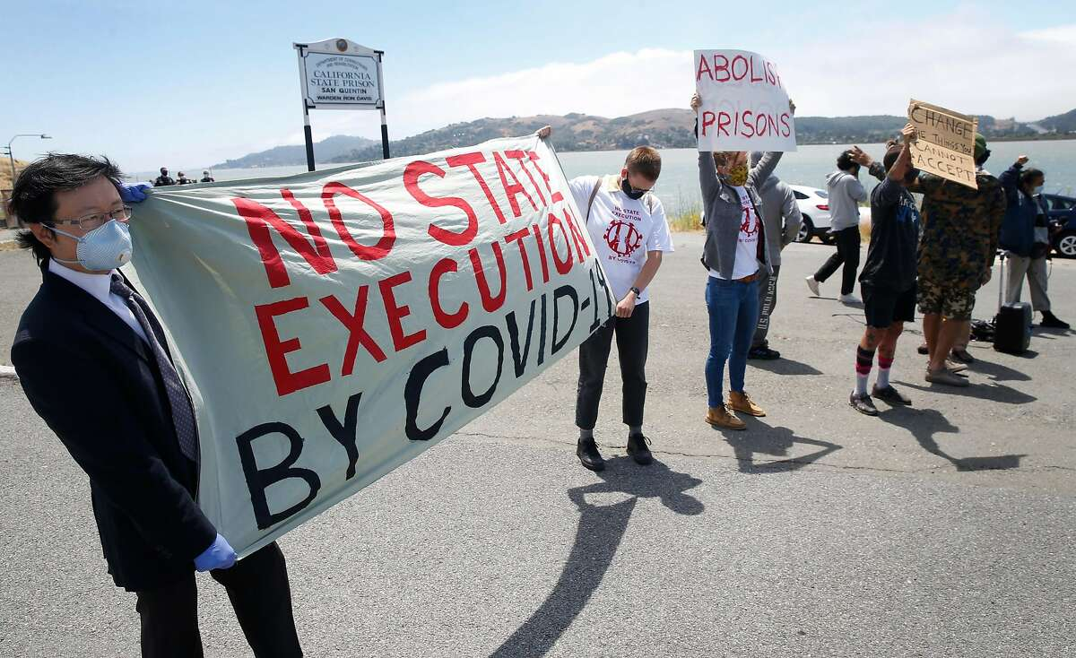 Richard Tan (left), co-organizer of the event, and Kayla Hunnewell display a banner as a caravan of cars carrying more than 200 protesters drives past the west gate of San Quentin State Prison in Larkspur, Calif. on Saturday, June 20, 2020 to demand protection for prisoners after COVID-19 cases exploded at San Quentin after the transfer of infected prisoners from Chino.
