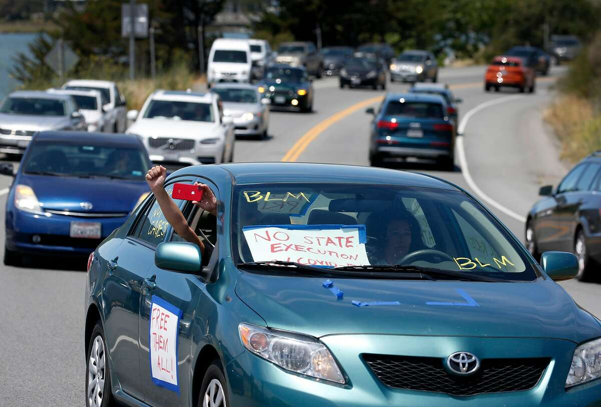 A caravan of cars carrying more than 200 protesters drives past the west gate of San Quentin State Prison in Larkspur, Calif. on Saturday, June 20, 2020 to demand protection for prisoners after COVID-19 cases exploded at San Quentin after the transfer of infected prisoners from Chino.