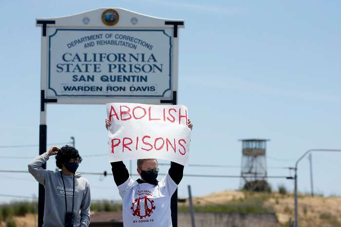 Kayla Hunnewell displays a message a a caravan of cars carrying more than 200 protesters drives past the west gate of San Quentin State Prison in Larkspur, Calif. on Saturday, June 20, 2020 to demand protection for prisoners after COVID-19 cases exploded at San Quentin after the transfer of infected prisoners from Chino.