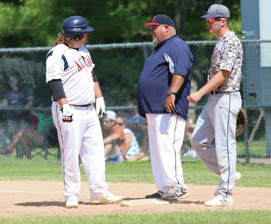 Alton coach Brian Hanslow (middle) talks with his son Tank Hanslow (left) after he reaches first base in a game last Sunday in Washington, Missouri. At right is Valmeyer first baseman Philip Reinhardt. Photo: Greg Shashack | The Telegraph