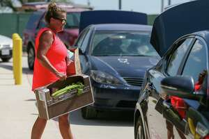 """Kitty Hawk Middle School teacher Cindy Hubbard helps distribute boxes of food to district residents in the Judson ISD """"Kick Off to Summer Food Drive"""" at the school on June 8."""