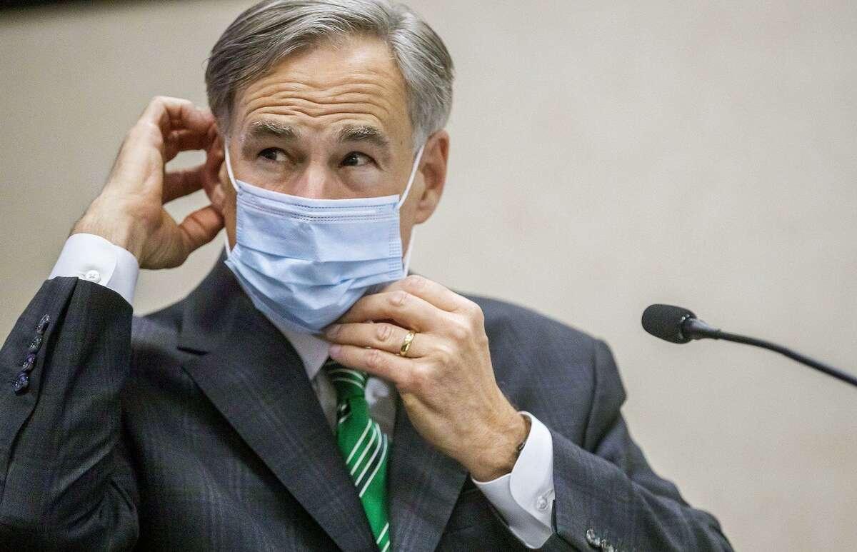 Texas Gov. Greg Abbott adjusts mask during Tuesday update on coronavirus in Texas. (Ricardo Brazziell/Austin American-Statesman/TNS)
