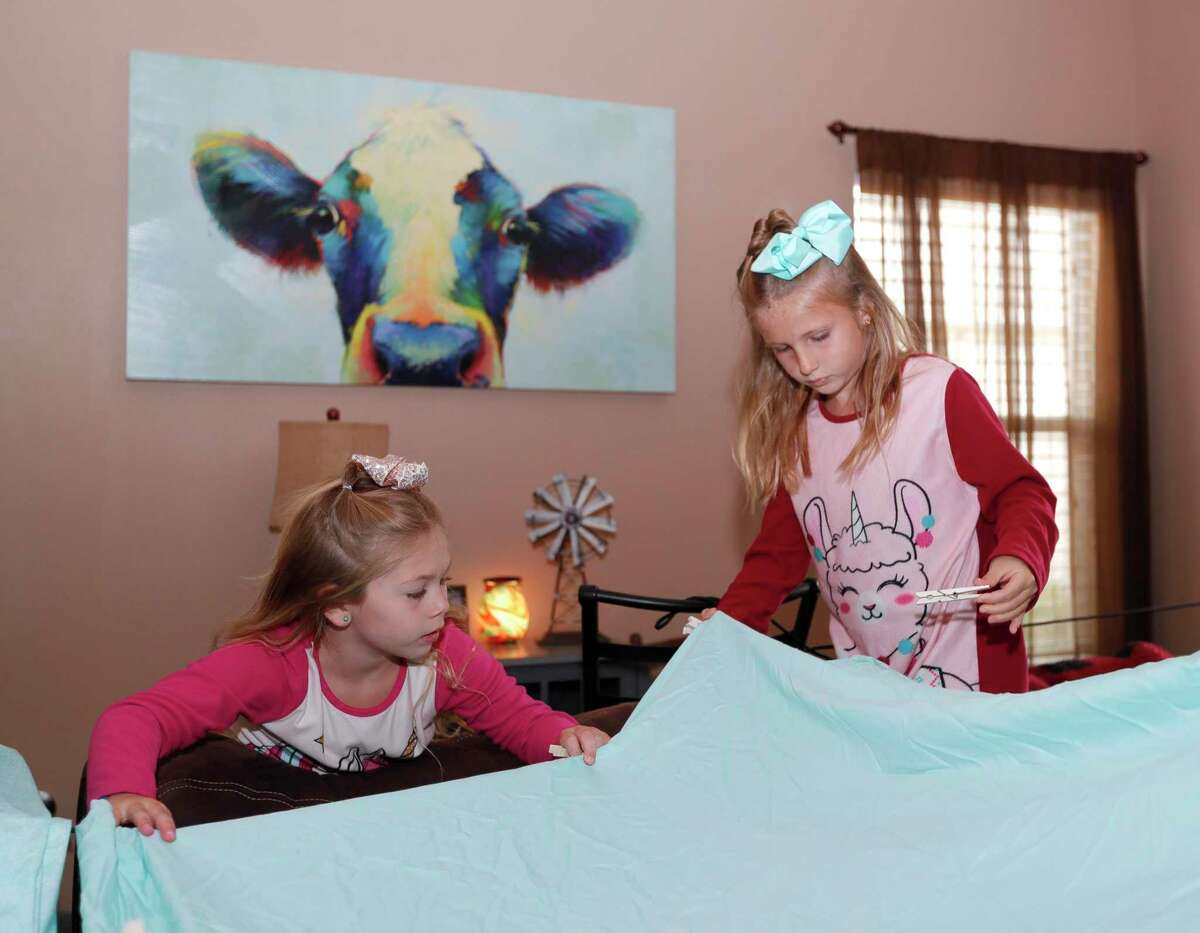 """Paisley Smart, left, helps her sister, Adalynn, secure a blanket fort in their living room as part of Family Promise of Montgomery County's """"Night Without A Bed"""" initiative, Saturday, June 20, 2020, in Montgomery. The nation-wide event is to raise awareness of children and family battling homelessness."""