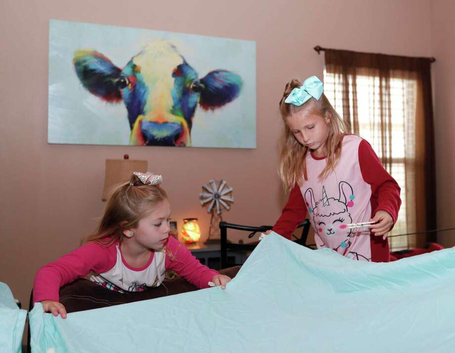 "Paisley Smart, left, helps her sister, Adalynn, secure a blanket fort in their living room as part of Family Promise of Montgomery County's ""Night Without A Bed"" initiative, Saturday, June 20, 2020, in Montgomery. The nation-wide event is to raise awareness of children and family battling homelessness. Photo: Jason Fochtman, Houston Chronicle / Staff Photographer / 2020 © Houston Chronicle"