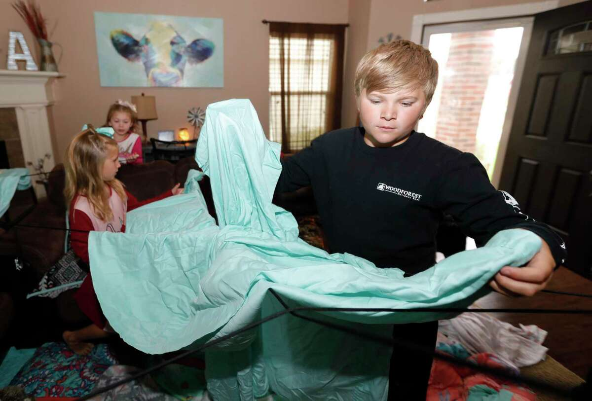 """Logan Smart helps his sisters, Adalynn and Paisley, set up a blanket fort in their living room as part of Family Promise of Montgomery County's """"Night Without A Bed"""" initiative, Saturday, June 20, 2020, in Montgomery. The nation-wide event is to raise awareness of children and family battling homelessness."""