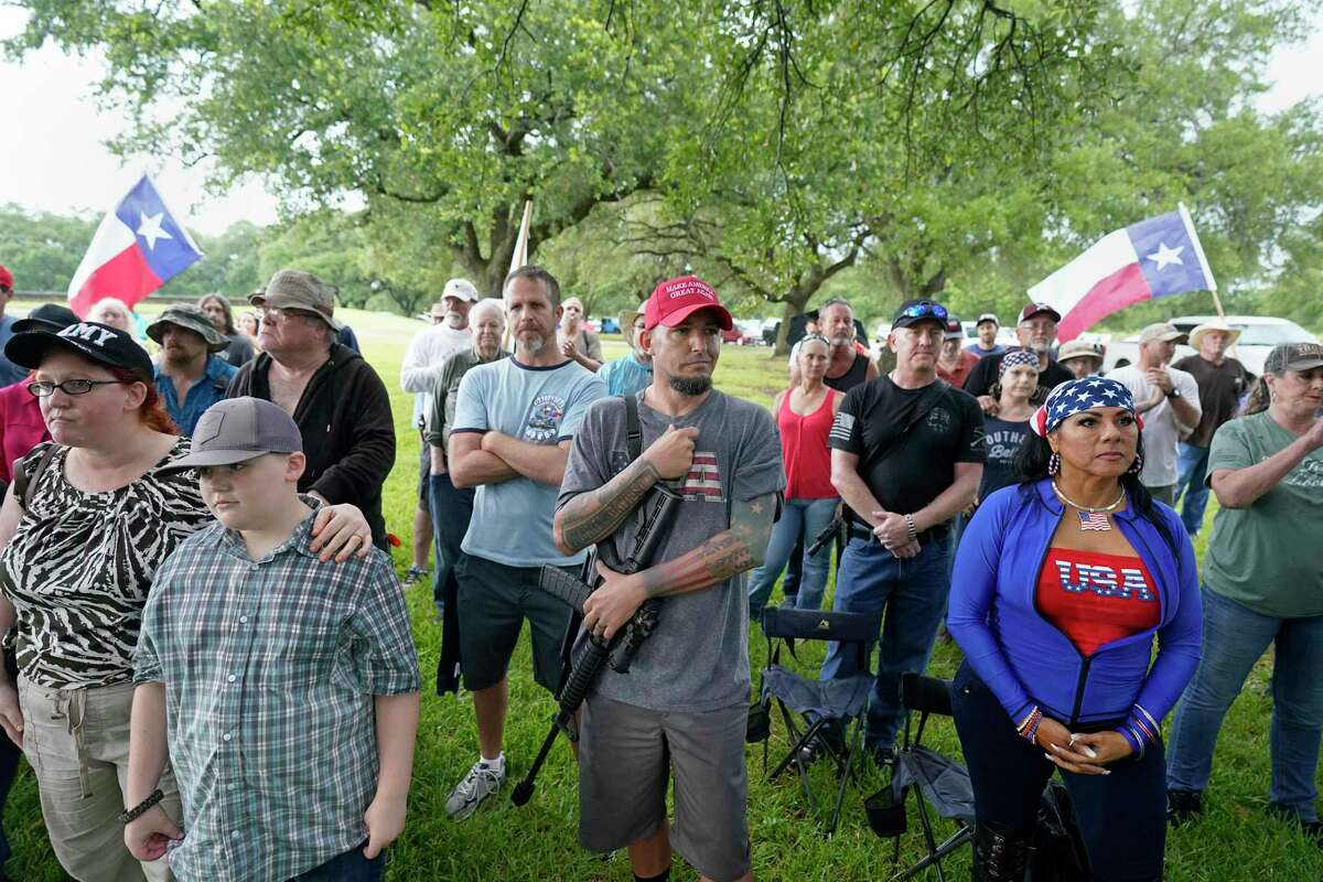 Clint Buss of Baytown, center, holds an AR-15 rifle during the This Is Texas Freedom Force rally at the San Jacinto Monument on Saturday. The group gathered to guard the monument.