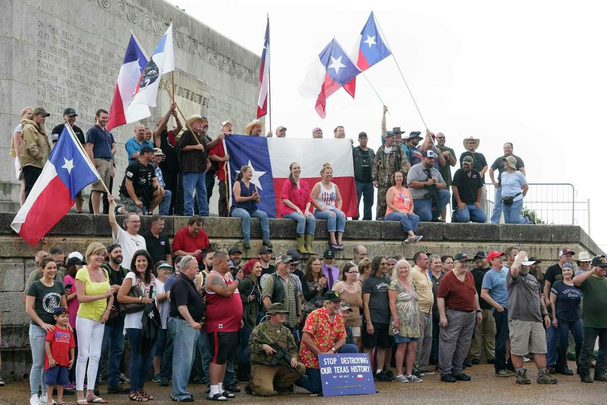 People gather for group photos and a video during the This Is Texas Freedom Force rally at the San Jacinto Monument on Saturday.