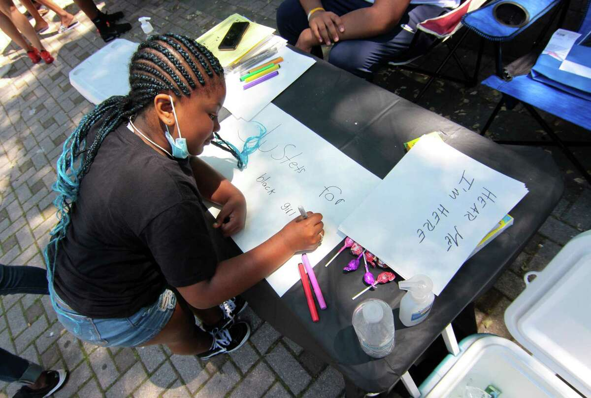 Ta'rahji Preston, 8, makes a protest sign so she can take part in a