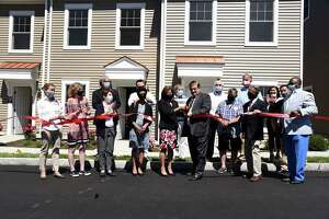 Last weekend's ribbon cutting to unveil 18 new townhouses at Armstrong Court had a big crowd on hand. Front row, from left, Selectwoman Jill Oberlander, Selectwoman Lauren Rabin, State Rep. Livvy Floren, CT Housing and Finance CEO Nandini Natarajan, Commissioner of the Department of Housing Seila Mosquera-Bruno, Chairman of the Housing Authority Board of Commissioners Sam Romeo, Commissioner Angelo Pucci, First Selectman Fred Camillo and HATG Executive Director Tony Johnson. Back row, from left, Commissioner Bob Simms, former Selectman Drew Marzullo, Commissioner Jim Boutelle, HATG Deputy Director Terry Mardula and State Rep. Stephen Meskers