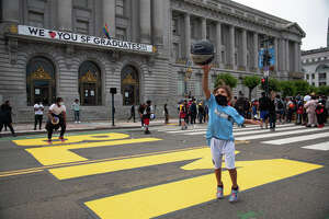 Niyati, Beaver, 7, throws her basketball into the air while standing on a BLM mural painted in front of City Hall. Protesters dribble basketballs while marching to San Francisco City Hall during the Speak Up & Dribble protest in San Francisco, Calif. on June 20, 2020. The protest was organized to show solidarity within the basketball community for the Black Lives Matter movement.