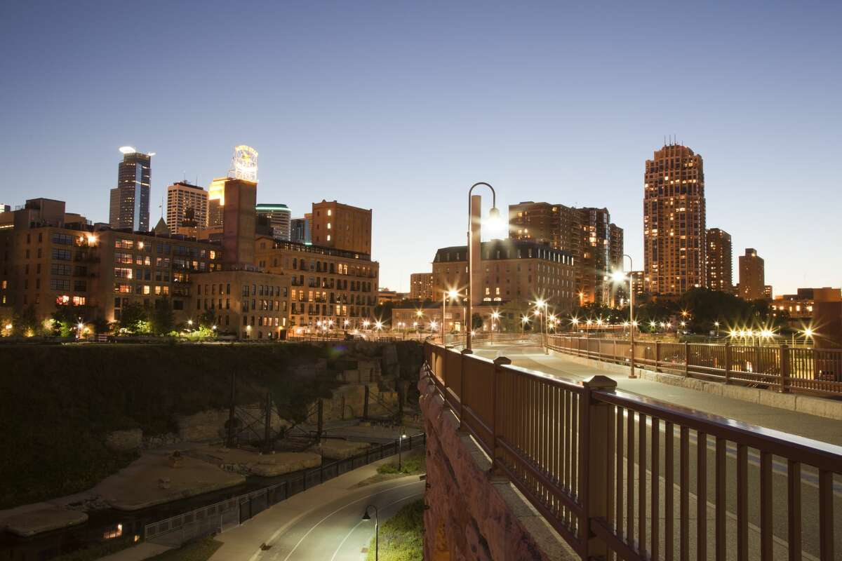View at dusk of Mill Ruins Park and footbridge next to Mississippi River looking towards the downtown skyline of Minneapolis.