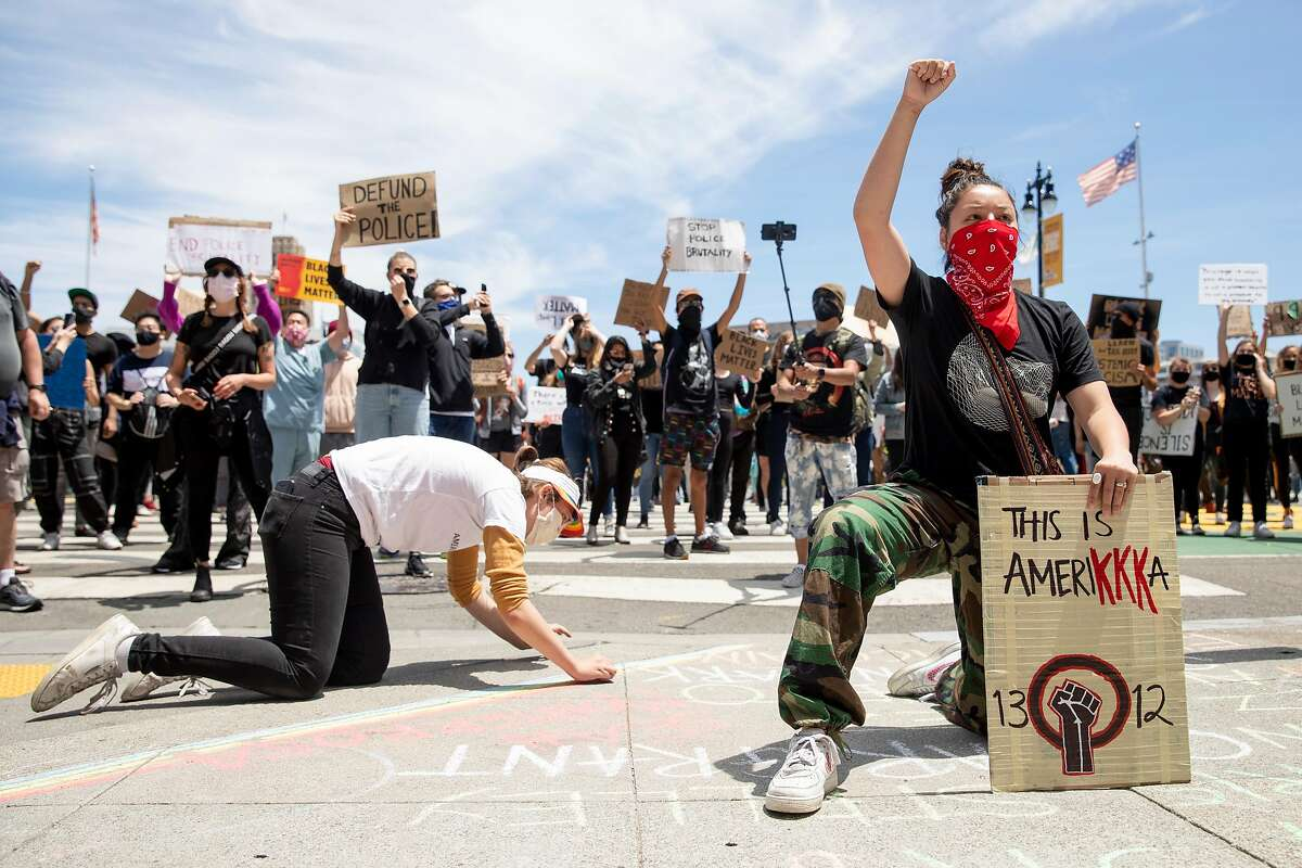 Zo' Zehnder, 15, of Menlo Park (right) kneels and raises her fist in front of City Hall after marching with hundreds down Market Street from the Ferry Building in solidarity with the Black Lives Matter movement, calling for the defunding of police, investment in Black communities and the resignation of President Trump held in San Francisco, Calif. Saturday, June 20, 2020.