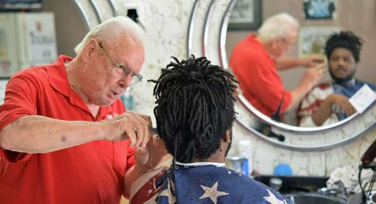 Don Fletcher cuts the hair of brand-new customer Phillip McCardy of Alton. This year marks the 60th that Fletcher has cut hair in Alton.