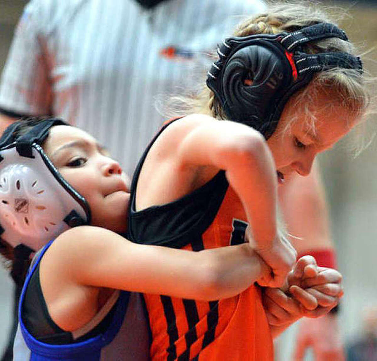 Avery Madison, 7, right, of the Edwardsville Wrestling Club tries to escape her opponent's grasp during an Edwardsville Open bantam division match in January.