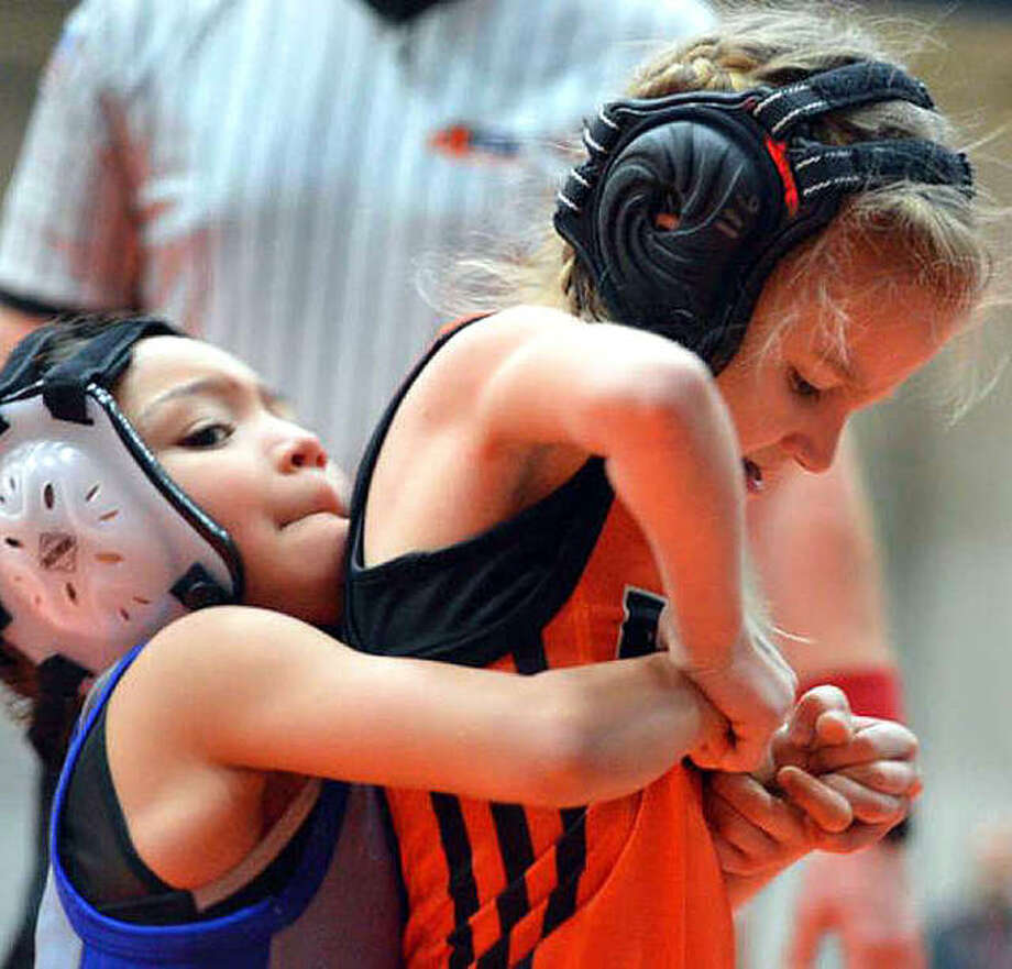 Avery Madison, 7, right, of the Edwardsville Wrestling Club tries to escape her opponent's grasp during an Edwardsville Open bantam division match in January. Photo: Scott Marion | For The Telegraph