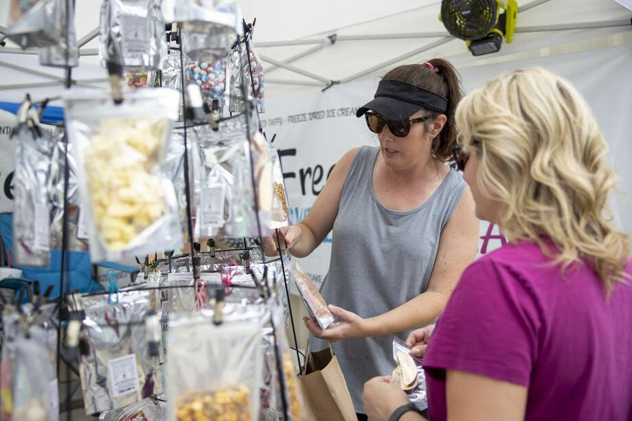 Brooke Simmons with Oso Goody explains their freeze dried goodies to a customer during a farmers market held in Magnolia, Sunday, June 21, 2020. Photo: Gustavo Huerta/Staff Photographer / Houston Chronicle © 2020