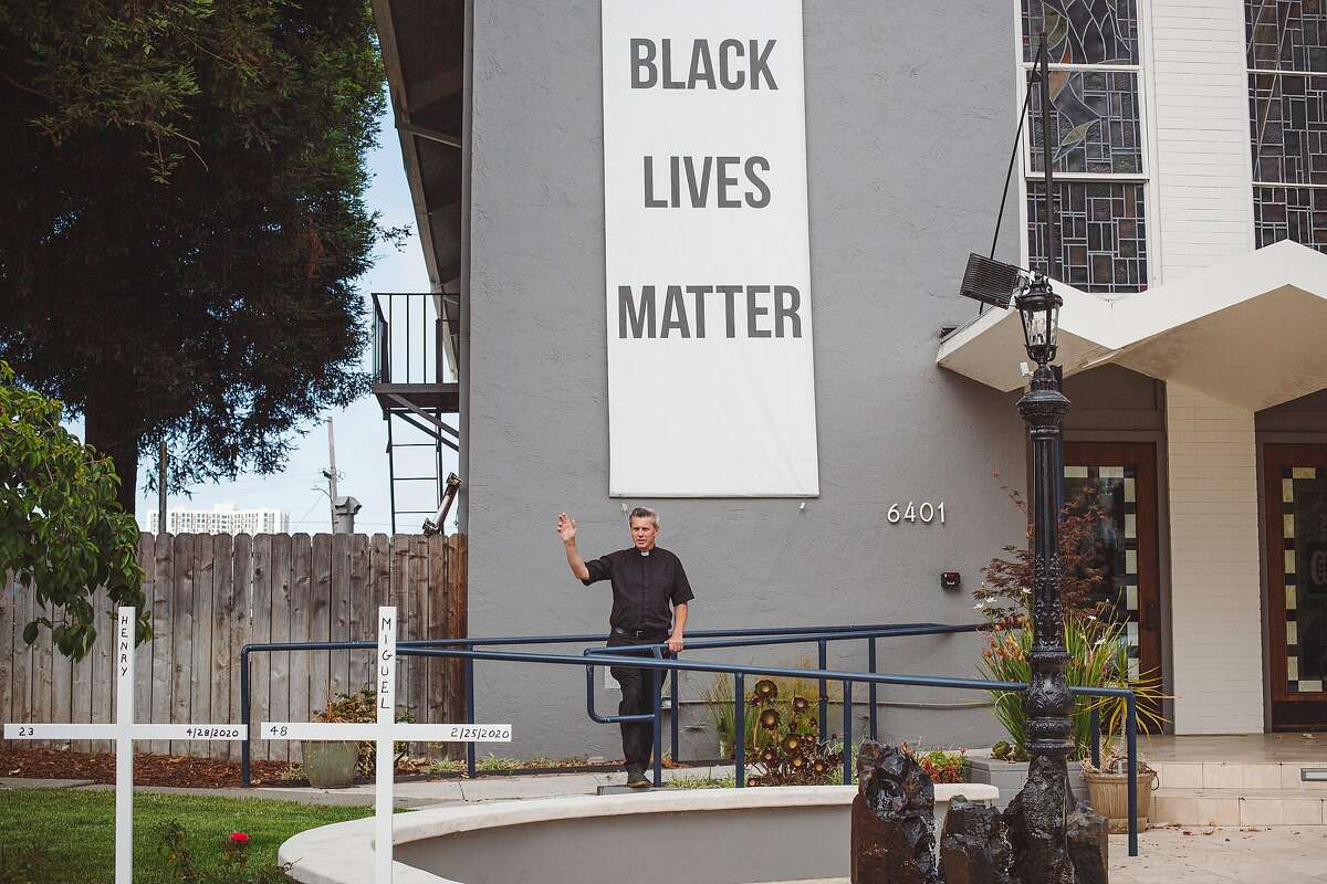 Father Aidan McAleenan stands in front of a Black Lives Matter banner at St. Columba Catholic Church in Oakland, Calif. on Friday, Jun. 19, 2020.