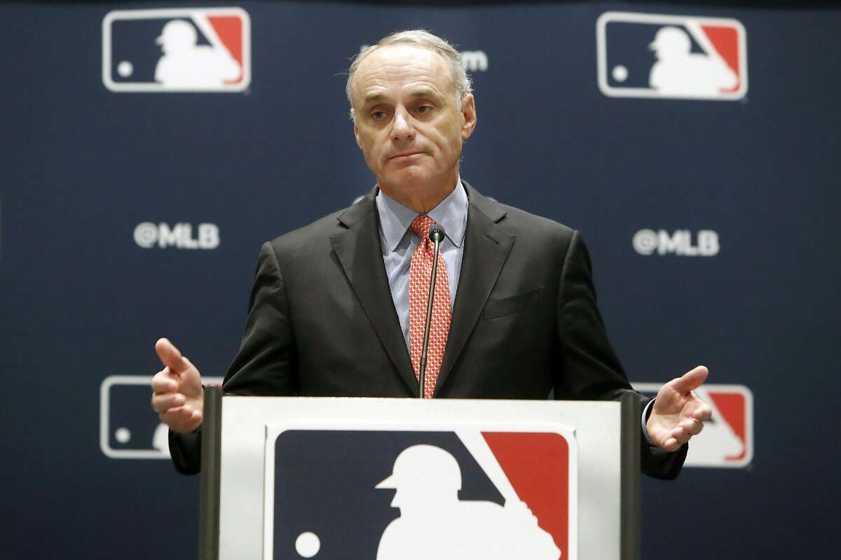 FILE - In this Nov. 21, 2019, file photo, baseball commissioner Rob Manfred speaks to the media at the owners meeting in Arlington, Texas. It's been over three months since the commissioners of major sports cancelled or postponed events because of the coronavirus. Enough time for us to grade them on how they've handled the virus so far. (AP Photo/LM Otero, File)