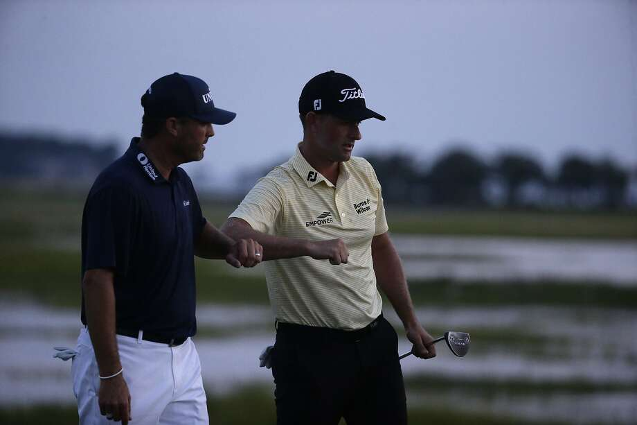 Webb Simpson (right) is congratulated by Ryan Palmer after finishing his round of 7-under-par 64 at Harbour Town. Photo: Gerry Broome / Associated Press