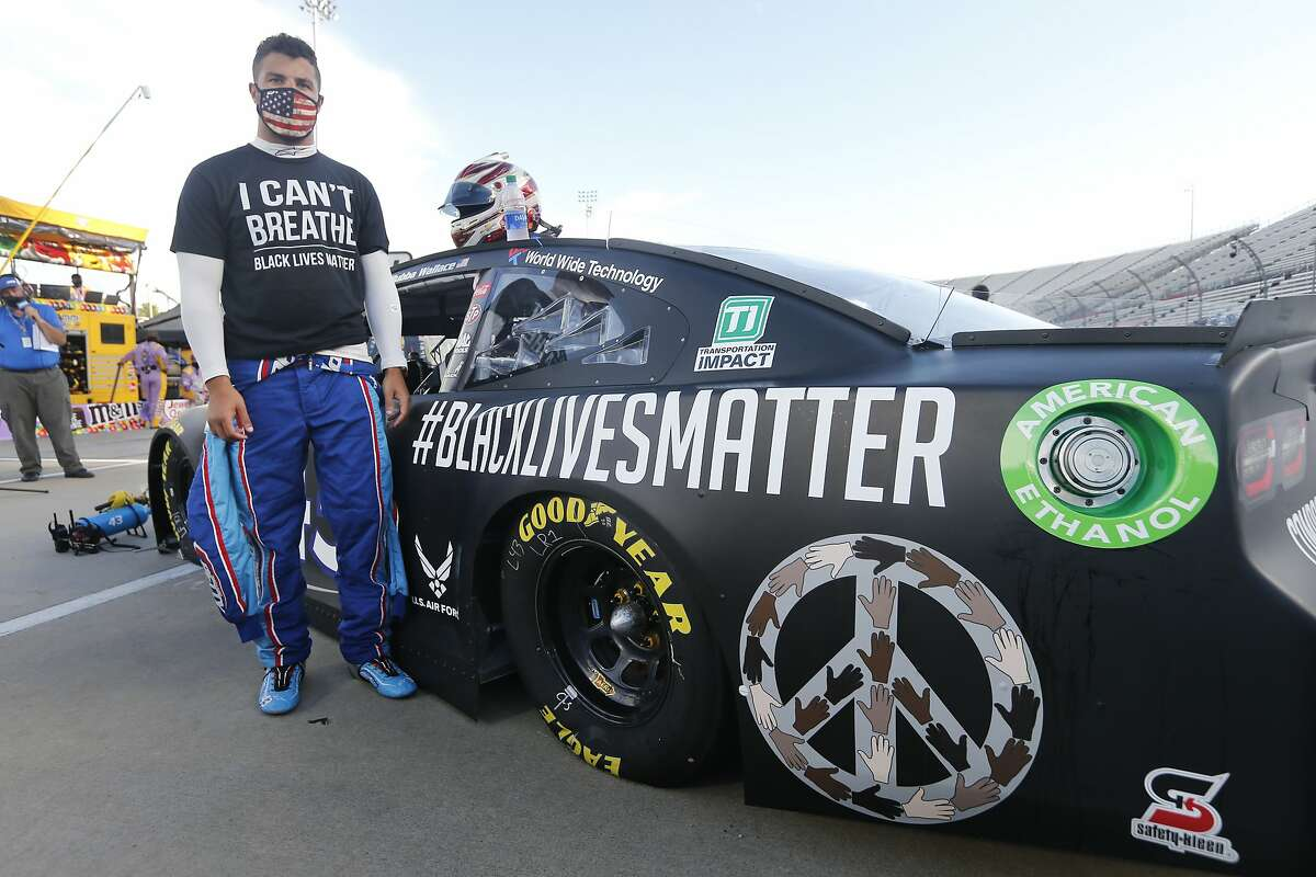 FILE - In this June 10, 2020, file photo, driver Bubba Wallace waits for the start of a NASCAR Cup Series auto race in Martinsville, Va. Bubba Wallace now counts Spike Lee and Demi Lovato - his admitted celebrity crush - as those loudly in his corner since he's become the leader of NASCAR's push for change. (AP Photo/Steve Helber, File)