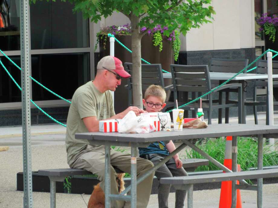Diners bring their own dinner to enjoy along Main Street on Saturday in downtown Midland. (Victoria Ritter/vritter@mdn.net)