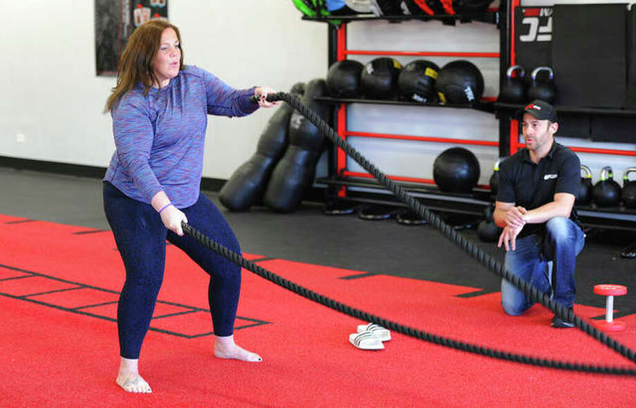 Colleen Tyrrell Llacsa works out at a gym in Naperville as trainer Matthew Kuschert looks on. She is working her way back from a medical incident that left her with a cerebral spinal fluid leak that caused numbness, weakness and double vision. Photo: Mark Welsh | Daily Herald (AP)