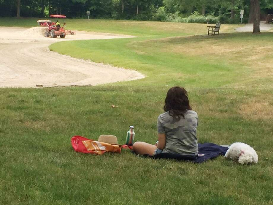 A woman has a picnic lunch with her dog at Merwin Meadows in Wilton, while a worker moves dirt around the pond, where swimming is discouraged due to the coronavirus pandemic. Photo: Patricia Gay /Hearst Connecticut Media /
