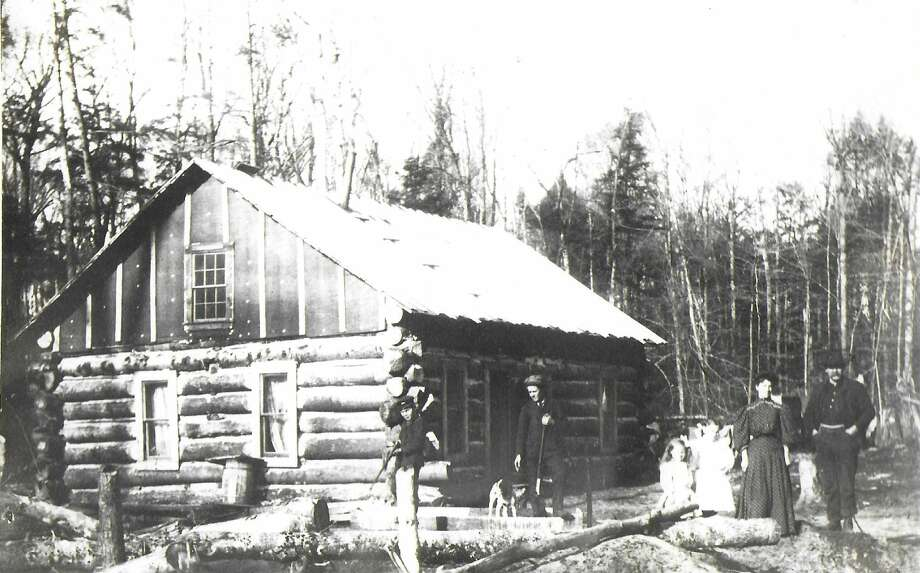One of the early rural Manistee County pioneer families pose in front of their log cabin home in the 1880s.