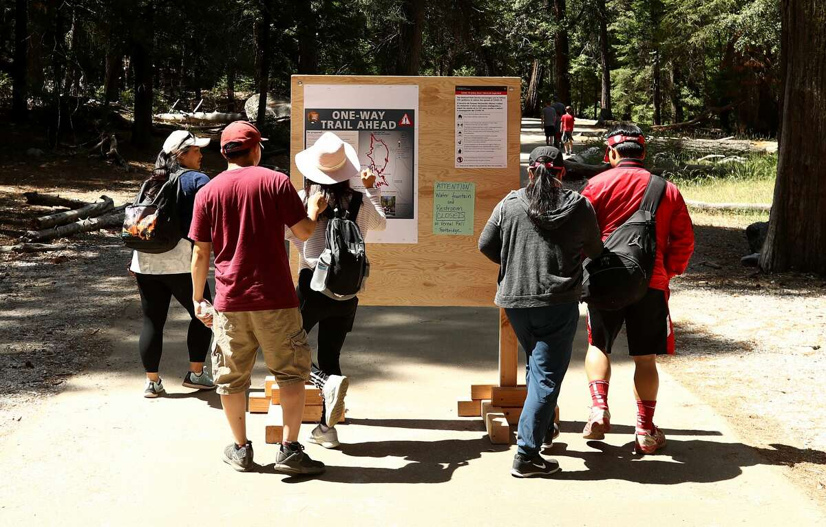 Visitors look at a sign that explains the one-way trail ahead on June 11, 2020, in Yosemite National Park, Calif.