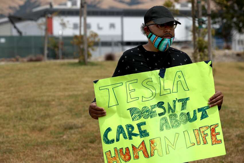 Tesla worker Carlos Gabriel,  holds a sign during a demonstration outside of the Tesla factory on June 15, 2020 in Fremont, California. He received a termination notice alleging a