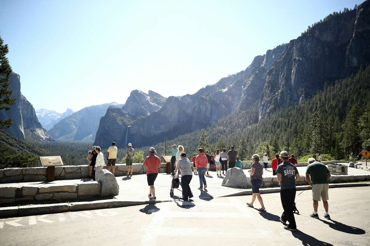 Visitors walk to the Tunnel View lookout on June 11, 2020, in Yosemite National Park, Calif.