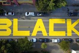 """An aerial photo shows the painted word """"Black"""" part of """"Black Lives Matter"""" giant street mural spanning three city blocks near City Hall in San Francisco, California on June 12, 2020. - The May 25 killing of George Floyd, an African American, by a white police officer in Minneapolis has ignited mass protests for racial justice and police reform across the United States. ("""